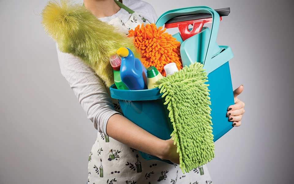 Close up of woman holding a bucket with cleaning supplies
