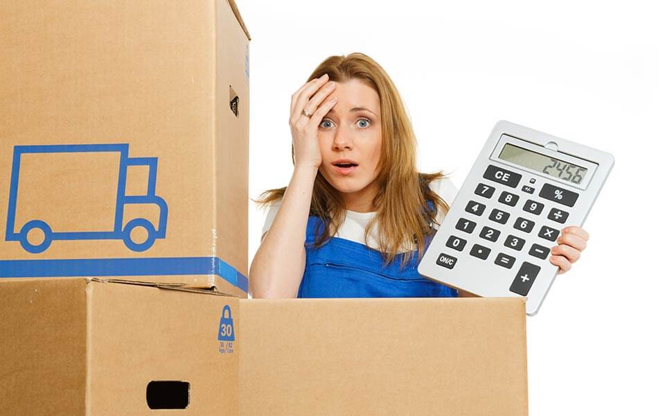 Woman with moving boxes holding a big calculator