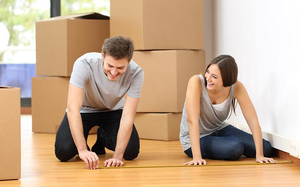 Couple measuring floor with moving boxes in the background