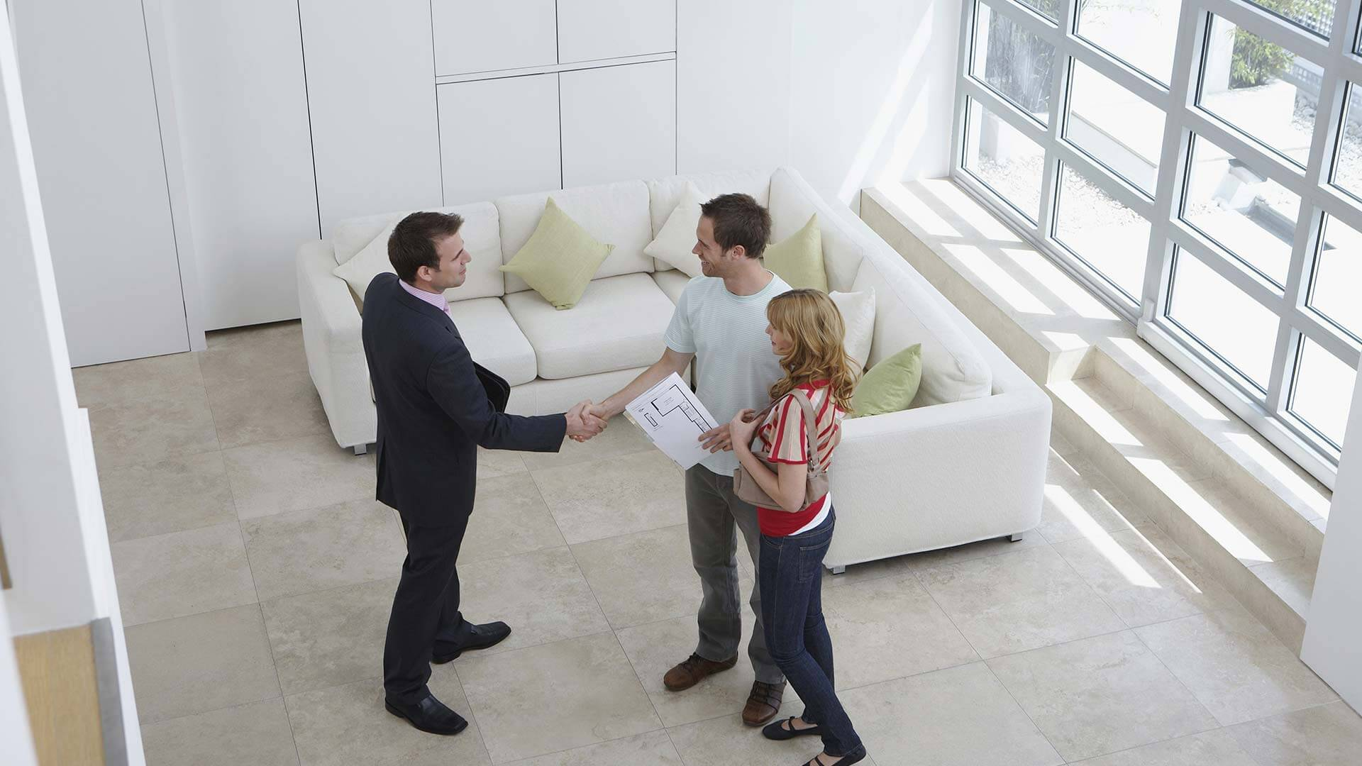 Estate agent shaking hands with tenants