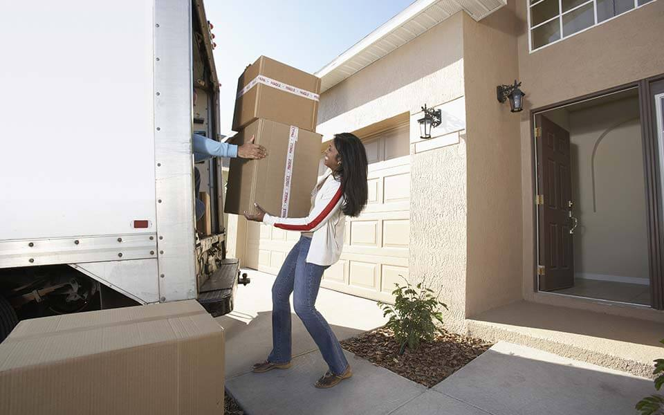 woman moving boxes into a truck
